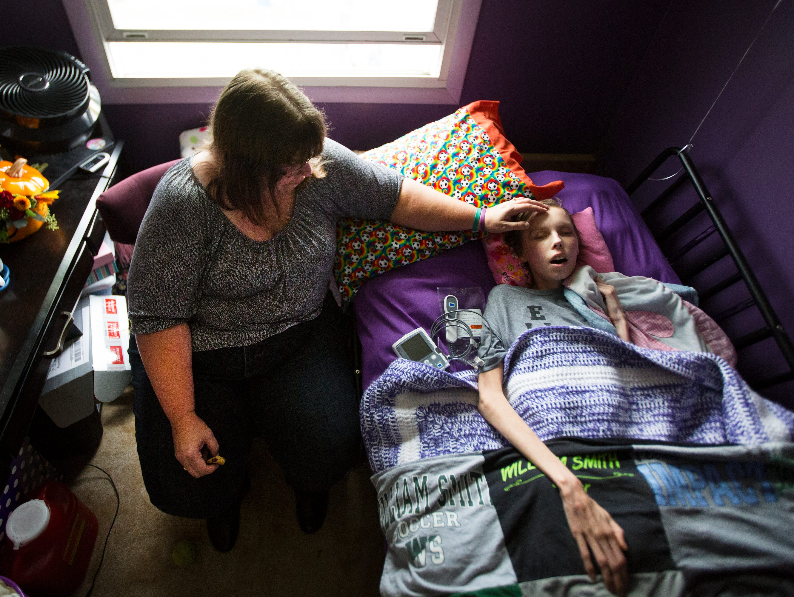 """Jamie Wagner lovingly touches Courtney's head as she rests in bed in their home in Farmington on Wednesday, October 21, 2015. """"You are perfect,"""" she repeated. """"I could stay here forever."""" Courtney, 18, has been battling brain cancer since she was 14."""
