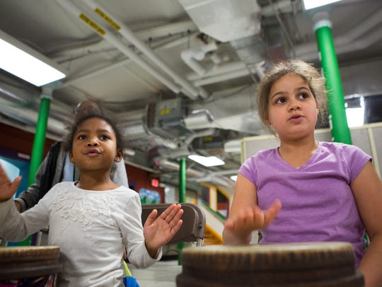 Kendra Davis, 6, and Yalexis Negron, 8, play hand drums