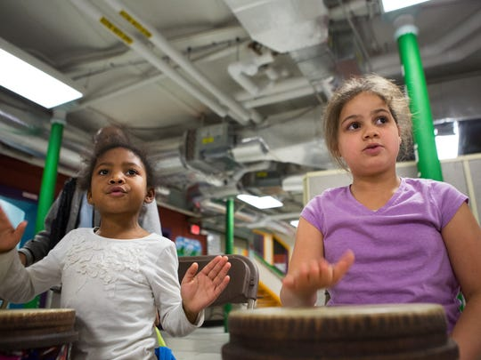 Kendra Davis, 6, and Yalexis Negron, 8, play hand drums during a ROCMusic class led by Eastman students at Edgerton Recreation Center on Thursday.