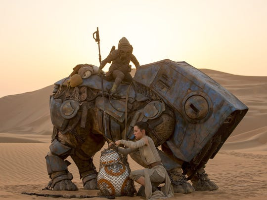 """Rey (Daisy Ridley) protects her little droid BB-8 in """"Star Wars: The Force Awakens."""""""