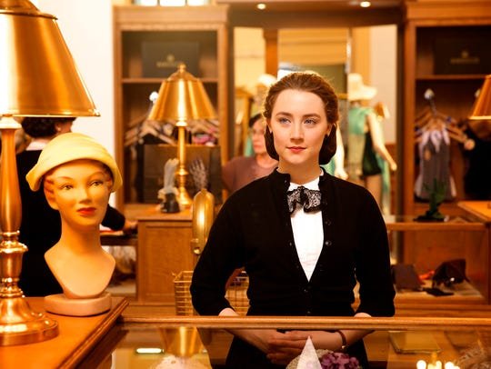 Eilis (Saoirse Ronan) mans a department store counter