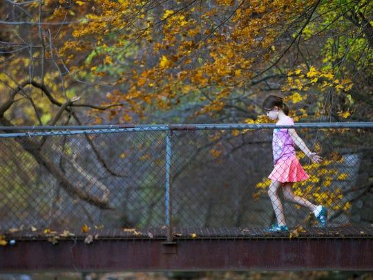 Callisto Daly, 8, of Rochester runs across a bridge while playing with a friend in Corbett's Glen Nature Park in Brighton on Nov. 4, 2015.