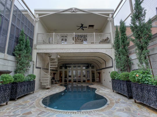 A stone courtyard and formal garden surround this indoor/outdoor pool and spa.