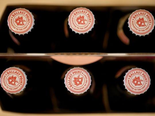 Bottles of Ballast Point beer sit on a shelf. New York-based