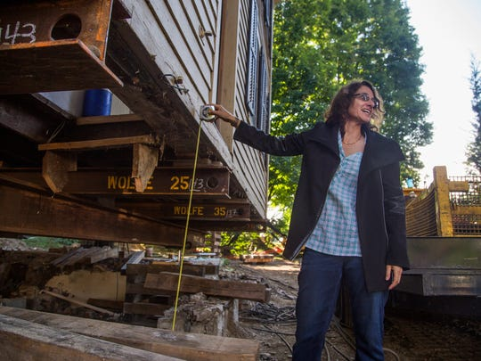 Homeowner Julie Nucci measures the progress as the elevation process neared completion on Sept. 17.