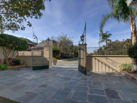 The home is accessed through iron gates.