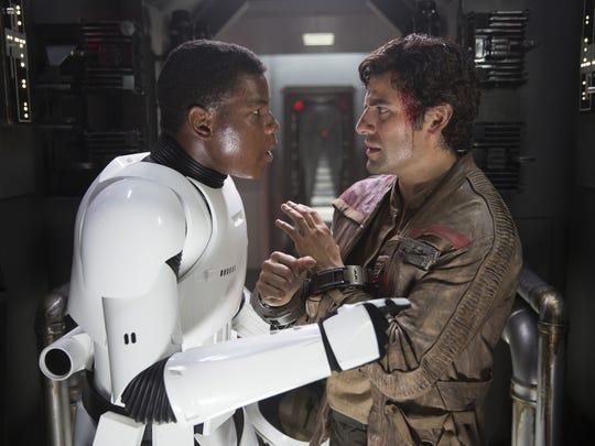 Finn (John Boyega, left) runs into Poe Dameron (Oscar Isaac) aboard a First Order ship in 'Star Wars: The Force Awakens.'
