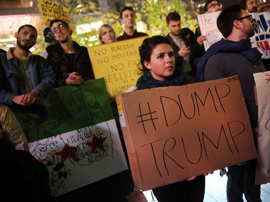 People listen to speakers at a demonstration against racism and conservative presidential candidate Donald Trump's recent remarks concerning Muslims on December 10, 2015 in New York City. Dozens or demonstrators and activists converged at Columbus Circle to denounce the politics of Trump and the treatment of Muslim refugees both in America and Europe.