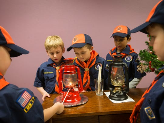 "Cub Scouts Cooper Hawk, 7, left, Cameron Maffucci, 6, Ayian Khan, 7, Wyatt Grogan, 7, and Thomas Drummond, 7, right, ""spread the flame"" at Iowa Religious Media Services in Urbandale, Thursday, Dec. 17, 2015. The flame originated in a grotto in Bethlehem close to the site where historians believe Jesus Christ was born."