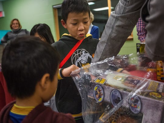 Ku Mu, 10, picks out a remote control truck of his liking as he shopped for toys at Zion Lutheran Church in Des Moines, Wednesday, Dec. 16, 2015. The church gave away presents to 600 children.
