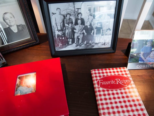 Family cookbooks sit on a table near family photographs