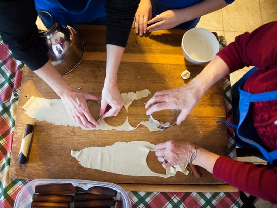 Melissa Ryan McBride and Mary Makowski cut out circles from cannoli dough as they continue their family tradition of making cannoli shells on Saturday, December 12, 2015.