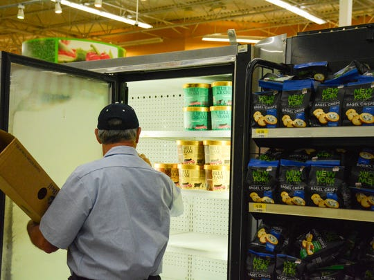 Darryll Cary stocks freezer with the first delivery of Blue Bell Ice cream  (Photo: Scott Clause, Special to The Advertiser)