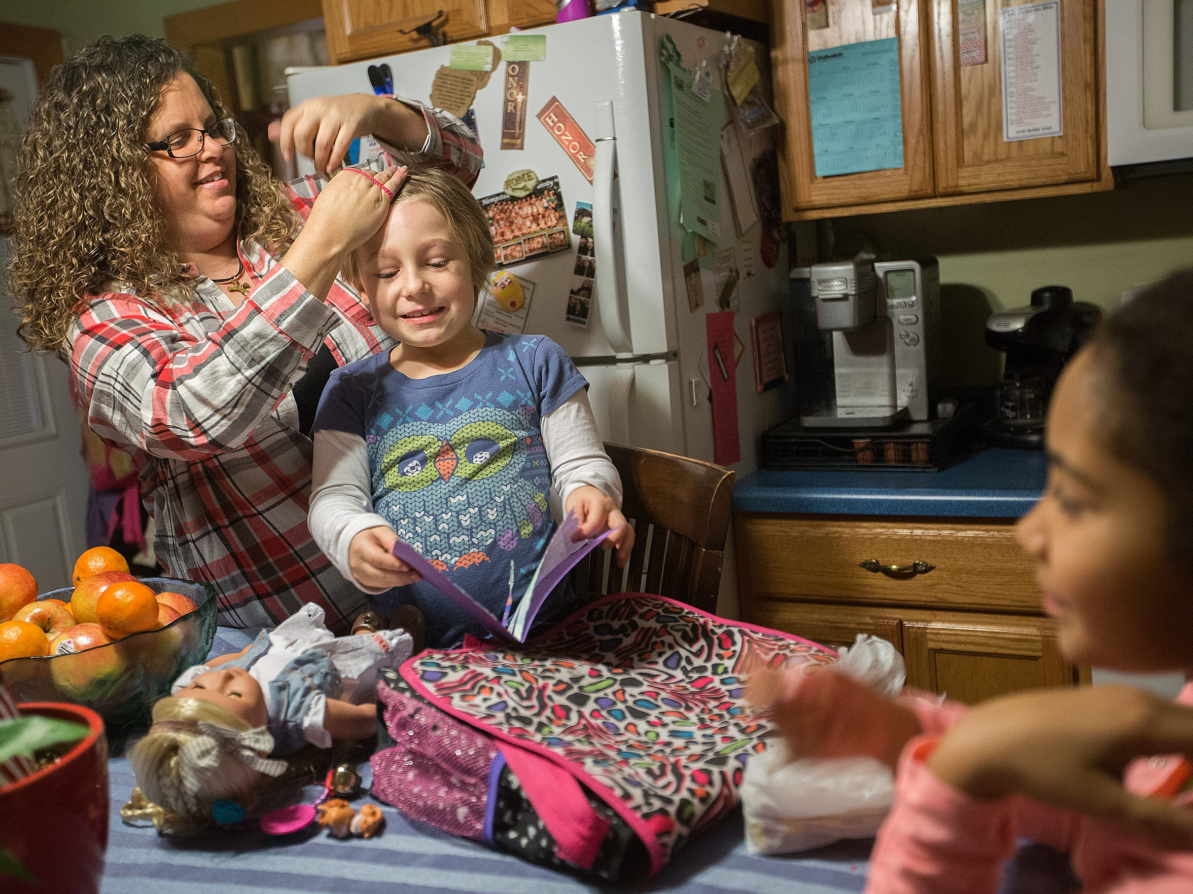 Karen Fox gets her adopted daughters Ella, 9, and Brenna, 7, ready to take to Fox's mother's apartment in Dubuque, Monday, Dec. 21, 2015. She has adopted three of the six girls she takes care of through the foster program.
