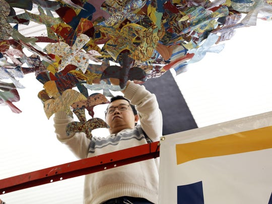 "Lead artist Bounnak Thammavong arranges a flock of small birds in the public art project ""Birds of a Feather"" at the Des Moines International Airport baggage claim area early in the morning of Dec. 24, 2015."