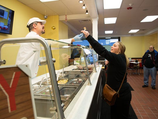 Co-owner David Piergiacomi hands Justine Kauffmann of Webster a sample of macaroni and cheese at The Original Mac & Cheez Shop in Webster on Thursday, January 7, 2016. Kauffman works at the Public Market and knows of their food from their food truck.