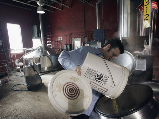 Frank Lassandrello adds hops to a batch of beer at the Goose Island Brewery.