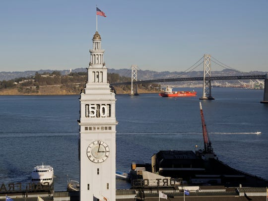 In this photo taken Wednesday, Dec. 16, 2015, is the Ferry Building in San Francisco. In the background is the San Francisco-Oakland Bay Bridge.  Atop the waterfront tower is the number 50 for the upcoming Super Bowl in February 2016.