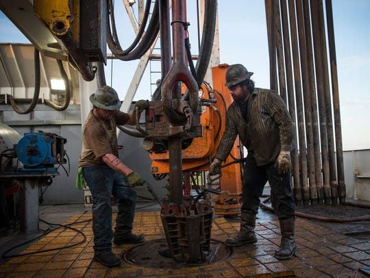 Workers with Raven Drilling line up pipe while drilling