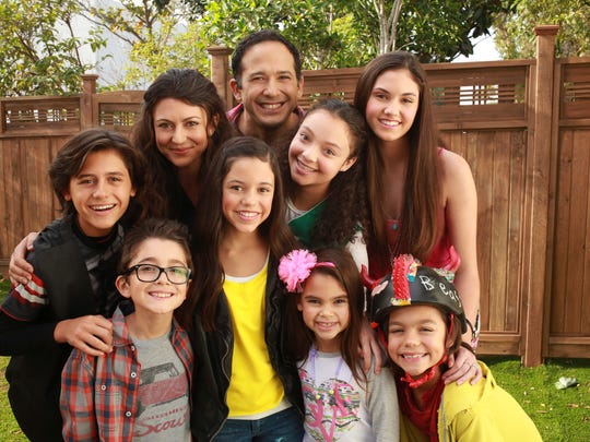"Jenna Ortega, (standing in the middle wearing a yellow shirt) plays Harley in the Disney show ""Stuck In The Middle"" and in this photo is surrounded by her TV family."