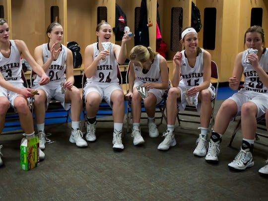 Members of the Western Christian's girls basketball team grab snacks in the locker room at halftime of Monday night's game against Central Decatur during the Iowa Girls' High School State Basketball Tournament at Wells Fargo Arena in Des Moines on Feb. 29, 2016.