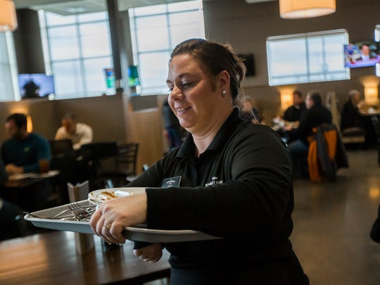 Hy-Vee employee Staci Stocker clears a tray of plates at the Hy-Vee Market Grille in Ankeny, Tuesday, March 1, 2016. Stocker has worked with the company for just over a year.