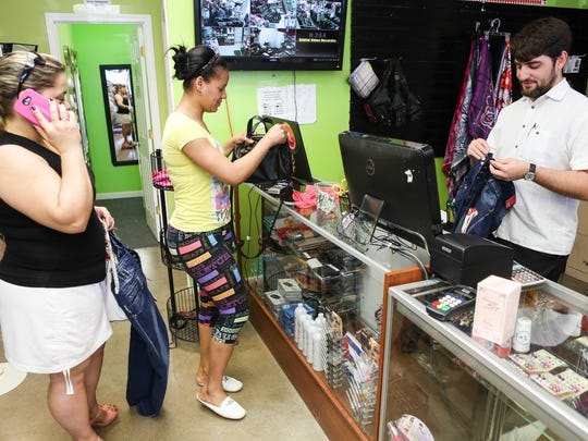 """Unlimited Electronics and Media employee, Luis Miranda, right, checks out customers Tuesday in the Cuban owned store located at 3415 Bardstown Road. Miranda's parents moved to America from Cuba and he has only visited the country twice. """"Everything here is better,"""" Miranda said. """"Cuba has been under a dictatorship and a blockade for 50 years. People are struggling there."""" Miranda has a deep appreciation for the culture and social life in Cuba, but feels many more Cubans will migrate to America in the coming years. """"Peope are taking the route of getting Visas and coming up through Latin America,"""" Miranda said.  March 15, 2016"""