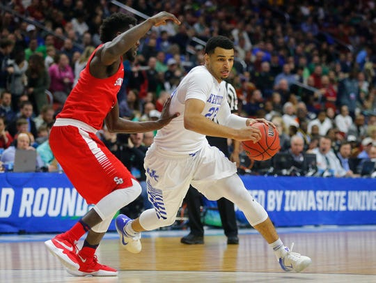 Kentucky's Jamal Murray drives the ball while being
