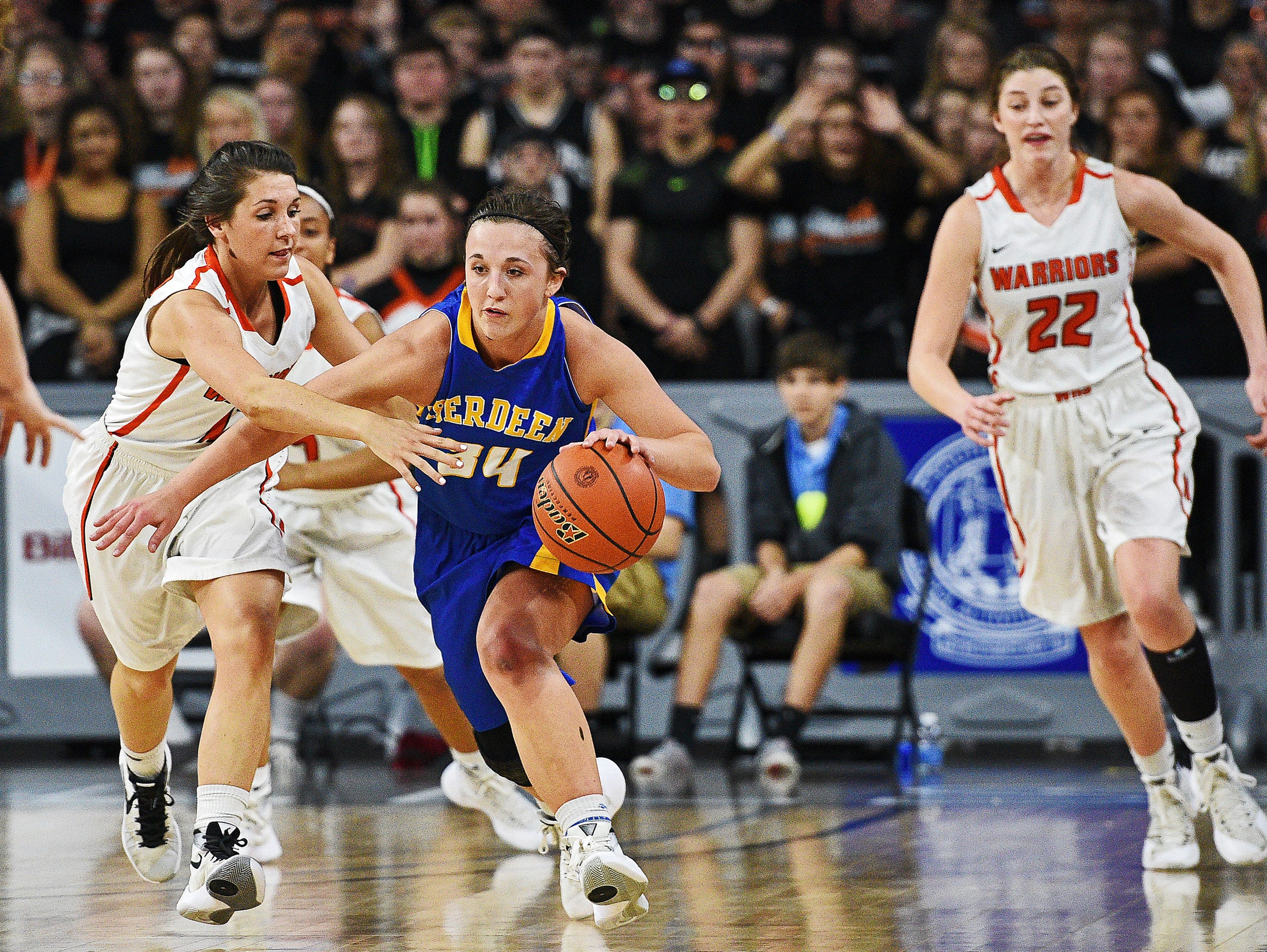 Washington's Kelsi Kearney (12) tries to steal the ball from Aberdeen Central's Brianna Kusler (34) during the South Dakota Class AA State Girls Basketball Tournament championship game Saturday, March 19, 2016, at the Denny Sanford Premier Center in Sioux Falls. Aberdeen Central beat Washington 75 to 64.
