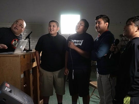 """In this March 8, 2016 photo, teacher Steve Shin, left, instructs a group of students singing during a music class at Stevenson Middle School in East Los Angeles. Los Angeles Unified School District, the nation's second largest, once had a $76.8 million budget for arts education, but years of cuts and layoffs wiped all arts classes from dozens of schools - leaving many students in the entertainment capital of the world with no music, visual arts, dance or theater instruction. That is slowly starting to change: The district is trying to enlist Hollywood studios to """"adopt"""" LA Unified schools and provide them with equipment, mentorships and training."""