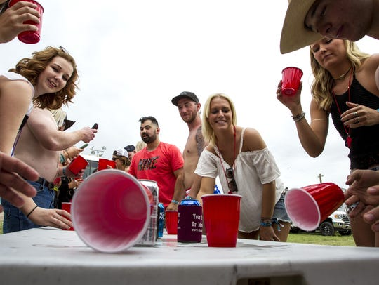 Festival-goers play a drinking game at a campsite