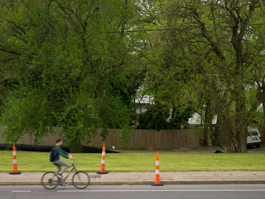 A bicyclist rides past a vacant lot near 12th and Wedgewood