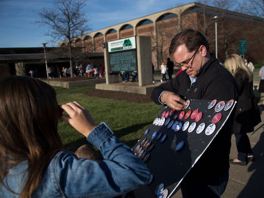Hillary Clinton campaign volunteer David Morrisson sells pins to people waiting to hear former president Bill CLinton speak at Binghamton University on Saturday, April 16, 2016.