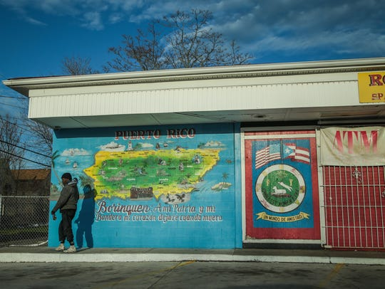 A man walks past a painted map of Puerto Rico on the