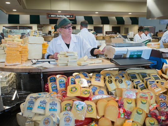 Kathy Ziesemer helps organize the cheese counter at The Fresh Market in  West Des Moines. The specialty grocer opened ;ast October.