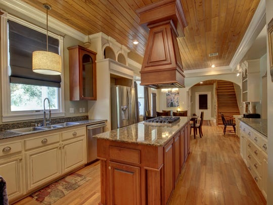 The kitchen is large with soothing colors and wood