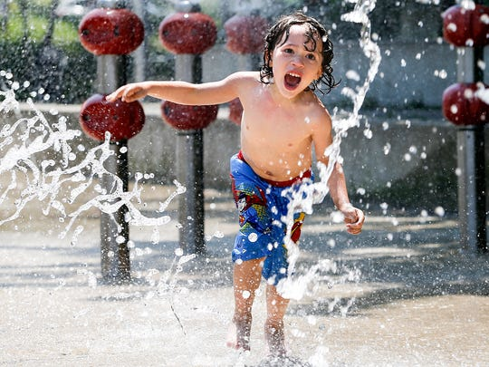 "Braylon Napier, 5, makes his way though a splash park at the Louisville Waterfront on Monday afternoon. After weeks of intermittent rain, many Louisvillians took advantage and opted outside to enjoy the sunshine and upper 70 temperatures. ""He's so excited to go swimming,"" Braylon's father, Chris Napier, said. ""He hasn't been swimming all winter and that's all he cares about."" 