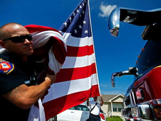 Captain John Hubbard (right) and firefighter Josh Jones of Joplin Fire Department Ladder 1 work to raise an American flag from their truck prior to the start of a ceremony in Cunningham Park in Joplin, Mo. on May 22, 2016 marking the fifth anniversary of the EF-5 tornado that hit the city in 2011.