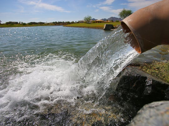Water pours from a metal pipe into a pond on the golf course at La Toscana Country Club in Indian Wells.