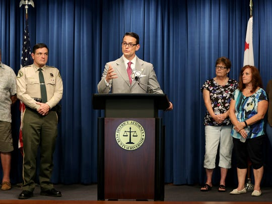 Riverside County District Attorney Mike Hestrin announces charges against two men in a decade-old triple homicide case in Pinyon Pines during a news conference in Riverside.