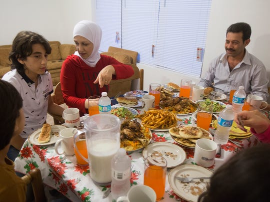 Gazweh Aljabooli, her husband Abdul Tameem, and their children Mohammad Natheer, 15, Sedra, 13, Mohamad Haidar, 11, Mutaz, 6, and Hala, 6, break their fasting as they celebrate the holy month of Ramadan, in their new apartment in Des Moines, June 15, 2016. They are Iowa's first Syrian refugee family. During Ramadan, Muslims fast from sunrise to sunset to commemorate the first revelation of the Quran to Muhammad according to Islamic belief.