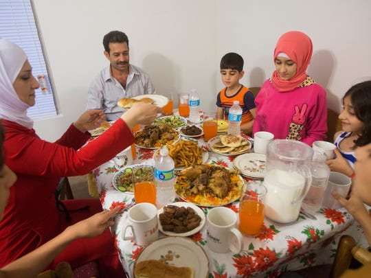 Gazweh Aljabooli, left, her husband Abdul Tameem, their children Mutaz, 6, Sedra, 13, Hala, 6, Mohamad Haidar, 11, and Mohammad Natheer, 15, break their fasting as they celebrate the holy month of Ramadan, in their new apartment in Des Moines, June 15, 2016. They are Iowa's first Syrian refugee family. During Ramadan, Muslims fast from sunrise to sunset to commemorate the first revelation of the Quran to Muhammad according to Islamic belief.