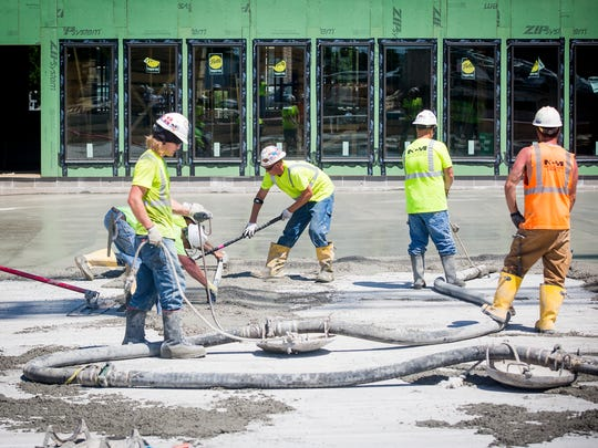 Construction workers finish concrete work the Confluence on Third apartment project in downtown Des Moines on Tuesday, June 21, 2016.