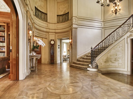 The foyer of the Stark estate features inlaid marble floors and ornate railings and moldings.
