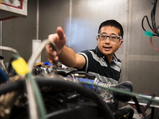 Zhe Wang, an automotive engineering graduate student, explains work he does on an engine at the Clemson University International Center for Automotive Research on Tuesday, July 19, 2016.