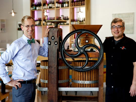 Cider Press Cafe general manager Roland Strobel, left, and executive chef Johan Everstijn flank an antique cider press at their former North Naples restaurant in March 2015.