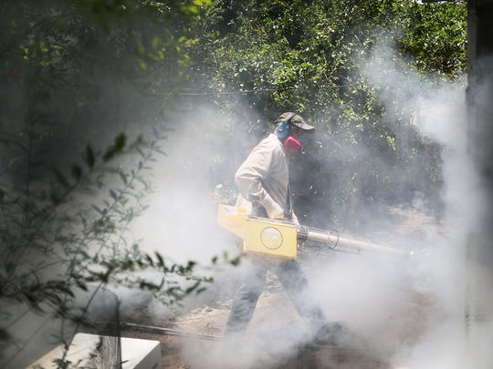 A Miami-Dade County mosquito control inspector sprays pesticide in the Wynwood neighborhood of Miami. The neighborhood is the site of the first outbreak in the U.S. caused by local mosquitoes.