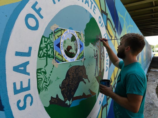 MIKE LAWRENCE / COURIER & PRESSMatt Fitzpatrick paints in details of the State Seal of Indiana as he and fellow artist Jon Whitman create a mural under the I-69 overpass recently. The mural is part of a effort by Keep Evansville Beautiful to address the gateways into the city, July 27, 2016.