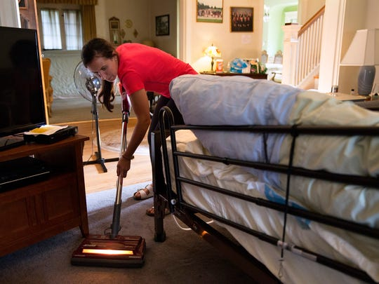 Molly Morris, 21, one of 92-year-old Margaret Coleman's 48 grandchildren, vacuums around her bed during a visit at the Coleman family home on July 25 in Chicago. Although she is on oxygen and can no longer walk, Margaret remains in high spirits and wishes to stay in the family house, so her children organize and take turns caring for her during the week. She also receives frequent visits from many of her 48 grandchildren and 13 great-grandchildren. (Erin Hooley/Chicago Tribune/TNS)