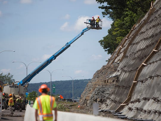 Crews work on preparing the retaining wall for its final coats of concrete along Route 17 West on Aug. 24.